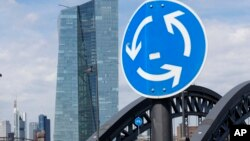 A traffic sign stands next to the headquarters of the European Central Bank in Frankfurt, Germany, June 16, 2015.