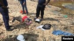 Policías de Curazao observan restos de ropa recuperados en una playa de la isla donde fueron encontrados los restos de cuatro venezolanos que perecieron en un naufragio el martes 9 de enero de 2018. Willemstad, Curazao, enero 11 de 2018.