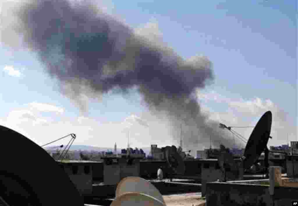This citizen journalism image provided by Aleppo Media Center AMC which has been authenticated based on its contents and other AP reporting, shows smoke rising from heavy shelling in Aleppo, Syria, Tuesday Feb. 12, 2013. Rebels captured a military air bas