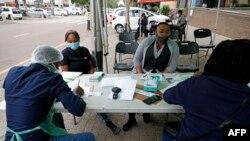 Un professionnel de la santé de la ville de Tshwane mène des exercices de dépistage sur des personnes avant de tester le coronavirus COVID-19 à Pretoria le 17 décembre 2020.