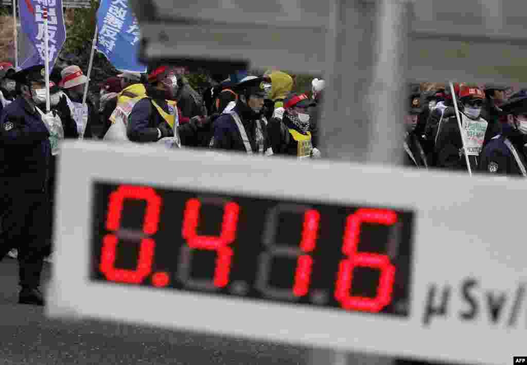 Марш протеста против ядерной энергетики. На мониторе показан уровень радиации в Корияме, префектура Фукусима
