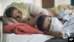 FILE - India experienced an outbreak of plague in September 1994 that killed 50 people. Above, a patient with plague symptoms, foreground, awaits test results with his mother at New Delhi's Infectious Disease Hospital.