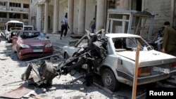 Security personnel walk in front of the former Interior Ministry building after a blast at Marjeh Square in Damascus, Syria, Apr. 30, 2013.