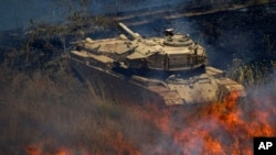 An old tank is surrounded by fire following explosions of mortar shells from Syria on the Israeli controlled Golan Heights, July 16, 2013.