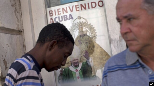 A poster showing Pope Benedict XVI, the Virgin of Charity of Cobre, Cuba's patron, is displayed on a window in Santiago de Cuba, Cuba, Sunday, March. 25, 2012.