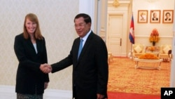 Rhona Smith, left, U.N. special rapporteur on the situation of human rights in Cambodia, poses with Cambodian Prime Minister Hun Sen, for a photo during a meeting at Peace Palace, in Phnom Penh, Cambodia, Monday, Sept. 21, 2015. Rhona on Monday met Hun Sen for her first mission to Cambodia after she replaced her predecessor Surya Prasad Subedi. (AP Photo/Heng Sinith)