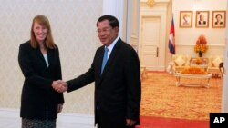 Rhona Smith, left, U.N. special rapporteur on the situation of human rights in Cambodia, poses with Cambodian Prime Minister Hun Sen, for a photo during a meeting at Peace Palace, in Phnom Penh, Cambodia, Monday, Sept. 21, 2015.