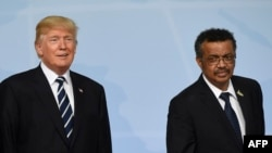 (L to R) French President Emmanuel Macron , US President Donald Trump and Director-General of the World Health Organization (WHO) Tedros Adhanom leave after posing a photo on the first day of the G20 summit in Hamburg, northern Germany, on July 7, 2017.