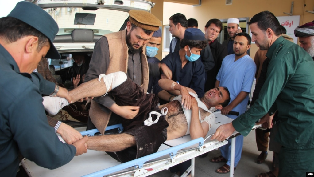 Afghan volunteers transport an injured man on a stretcher to a hospital following a bomb attack on a campaign rally in Afghanistan's northeastern Takhar province, Oct. 13, 2018.