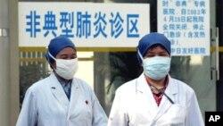 资料照:中国医务人员走过北京的一个非典肺炎诊区。(2003年4月29日)