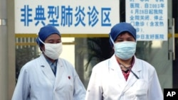 "FILE PHOTO - Chinese health workers wear protective garments and masks walk in front of the clinic marked as ""atypical pneumonia clinic zone"", Beijing, China."