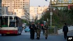 Cảnh sát vũ trang Trung Quốc tuần tra trên đường phố gần nhà ga xe lửa ở Côn Minh, nơi xảy ra vụ đâm chém chết người.