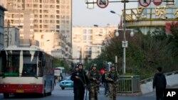 Polisi dan paramiliter bersenjata berpatroli dekat stasiun kereta api Kunming, tempat serangan penusukan yang menewaskan lebih dari 30 orang. (AP/Alexander F. Yuan)