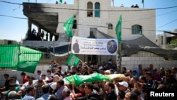 Palestinians carry the body of Amar Abu Aysha, who was shot dead by Israeli troops, during his funeral in the West Bank city of Hebron, Sept. 23, 2014.