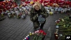 Một phụ nữ Ukraine tưởng nhiệm người bạn bị thiệt mạng trong các cuộc xô xát với cảnh sát hồi tháng 2 tại Quảng trường Độc lập ở Kiev.