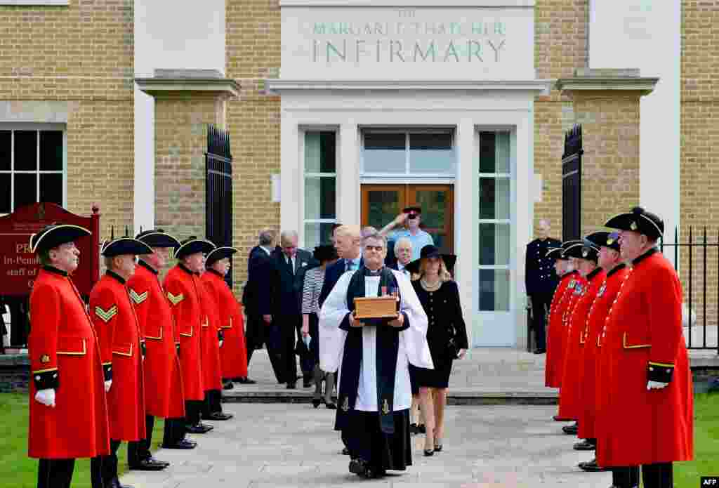 Reverend Richard Whittington carries an oak casket with the ashes of late British former Prime Minister Margaret Thatcher, ahead of her son Mark (L) and his wife Sarah (R) past an honor guard of Chelsea Pensioners after leaving the chapel at the Roya Hospital Chelsea to be laid to rest in the ground.