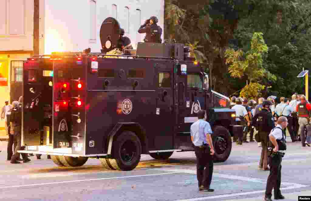 Police watch from an armored car as protesters gather after a shooting incident in St. Louis, Aug. 19, 2015.