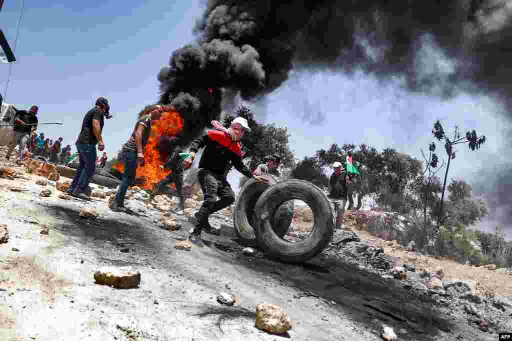 Palestinski demonstranti pale gume tokom sukoba sa izraelskim snagama bezbednosti, koje su usledile nakon nereda u selu Beita, južno od Nablusa, na okupiranoj Zapadnoj Obali. 11. juni, 2021. ( Foto: Džafar Aštijeh / AFP )