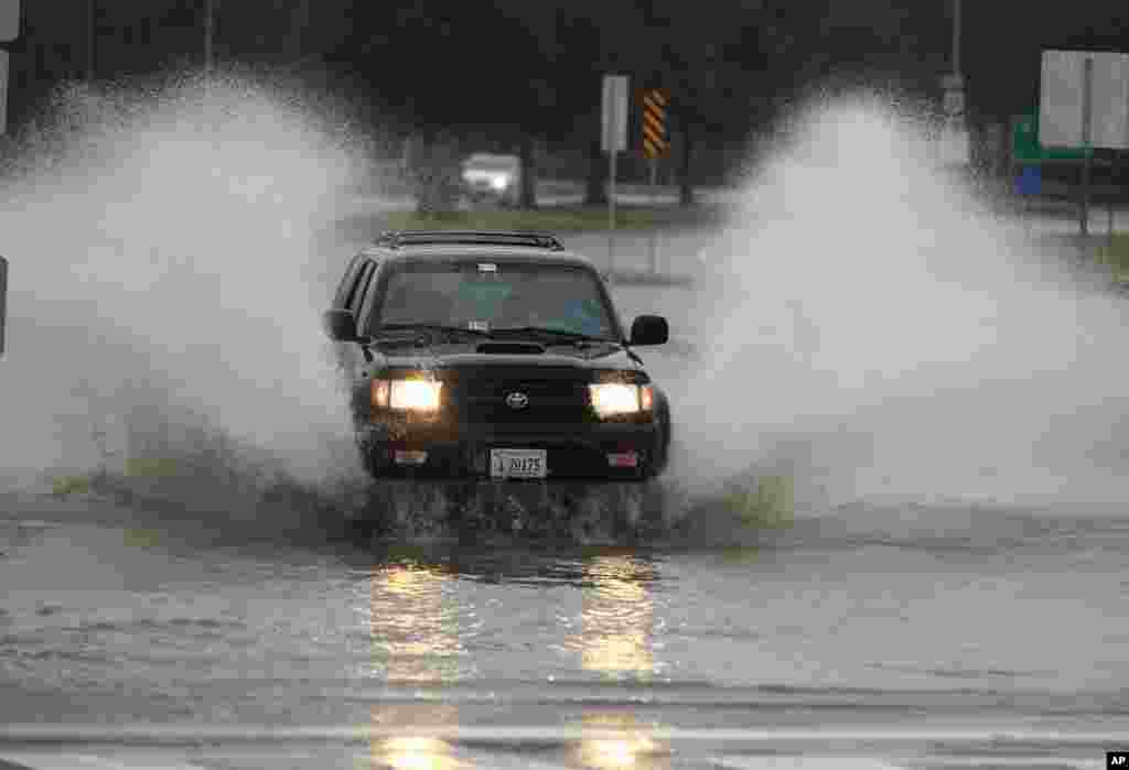 A car plows through a flooded street in the Ocean View area in Norfolk, VA., Sunday, Oct. 28, 2012.