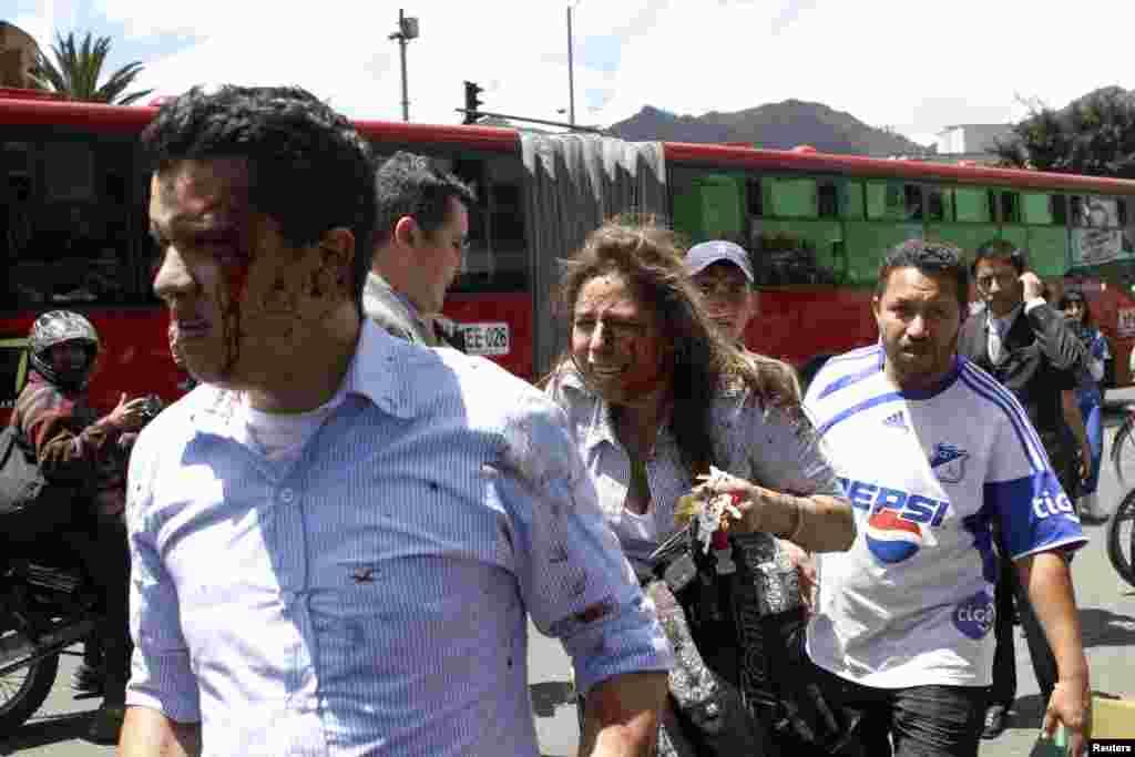 Heridos con sangre en sus rostros se alejan del lugar del atentado en Bogotá.