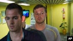 美国奥运游泳选手本茨(左)和康杰尔(右)离开里约国际机场的警察局