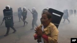 A protester escapes from riot police officers who fire tear gas grenades during a protest in Phnom Penh, Jan. 27, 2014.