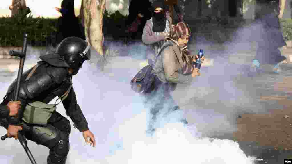 Women and police dodge tear gas during a protest at Al-Azhar University in Cairo, Dec. 11, 2013. (Hamada Elrasam for VOA)