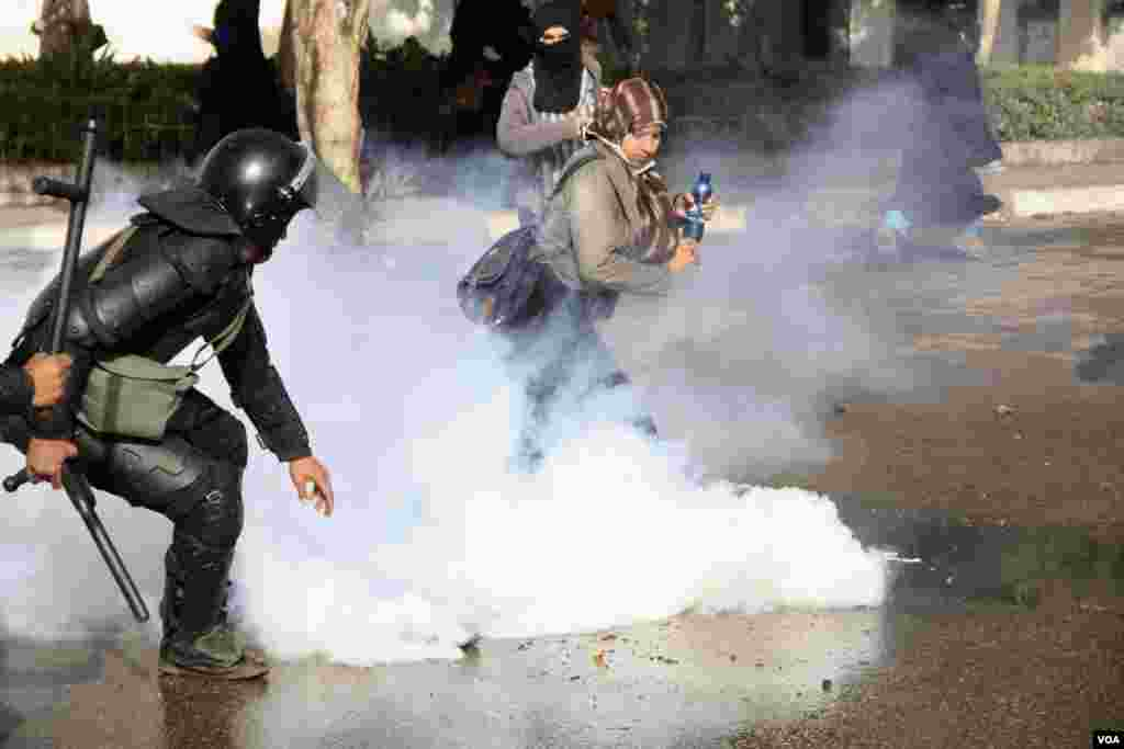 Women and police dodge tear gas during a protest at Al-Azhar University in Cairo, Egypt, Dec. 11, 2013. (Hamada Elrasam/VOA)