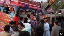 Nhân viên cứu hộ Pakistan giúp đưa hành khách ra khỏi chiếc xe khách bị đâm nát tại Pannu Aqil, ngày 20/4/2014.
