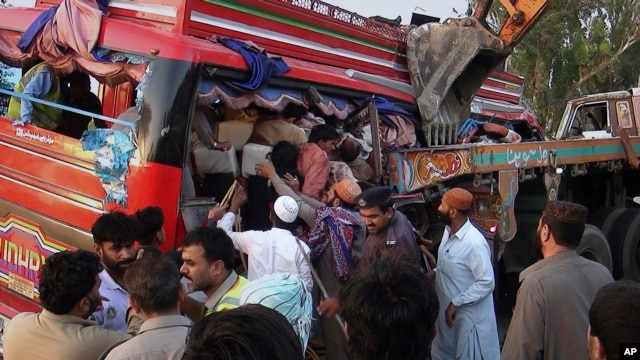 Pakistani rescue worker and volunteers gather to remove passengers from a damaged bus at the accident site in Pannu Aqil, Pakistan, Sunday, April 20, 2014.