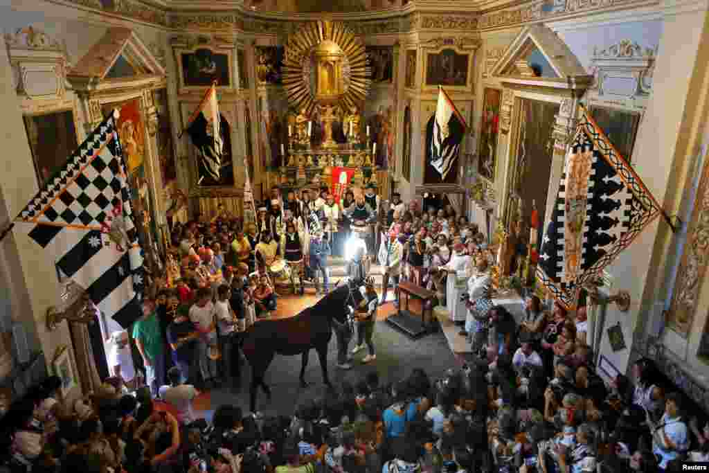 Supporters look at jockey Jonathan Bartoletti (C) and his horse, Bened of the Lupa (Wolf) during a blessing ceremony in a church, before the Palio race in Siena, Italy.