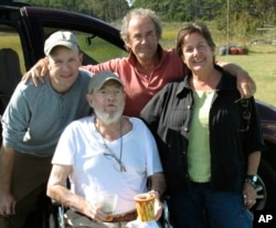 In this Sept. 29, 2009 photo provided by Betsy McNair, Robert McNair, center, poses with his children from left to right, Paul, Mark, and Betsy on the Eastern Shore of Virginia. (Courtesy of Betsy McNair via AP)
