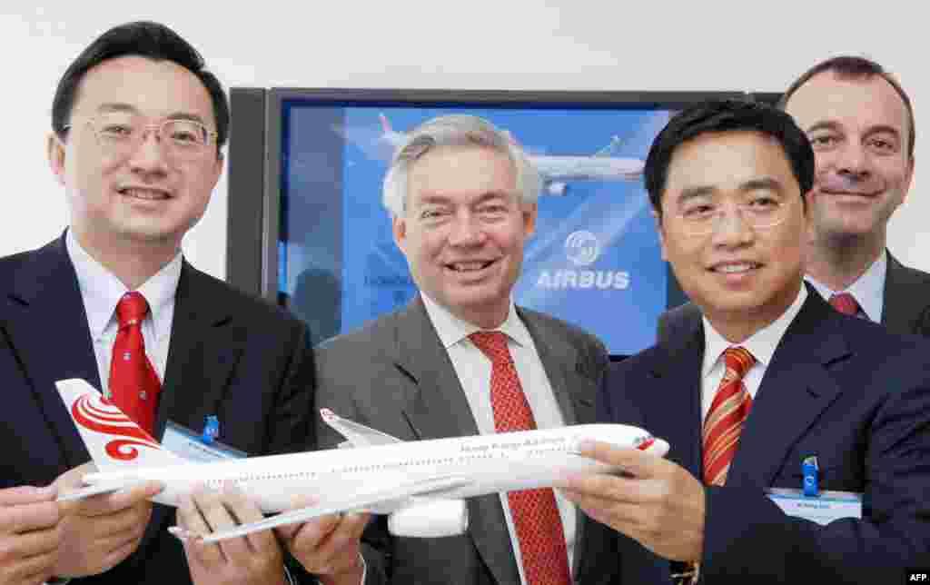 2007年6月21日,海航集团的子公司香港航空公司的董事长任卫东(音译)和王健(右起第二人)与空中客车公司的销售总监John Leahy在巴黎国际航空展期间签订合同之后合影。香港航空公司同意以目录价格从空客购买51架飞机,价值55亿美元(41亿欧元)。