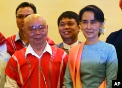 Myanmar's Foreign Minister Aung San Suu Kyi, right, and Mutu Say Po, chairman of Karen National Union (KNU) pose for photos during their meeting at a hotel in Naypyitaw, Myanmar, Aug. 24, 2016.