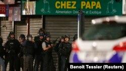 Polisi Perancis mengamankan wilayah dalam adu tembak di Saint-Denis, dekat Paris (18/11), dalam operasi berburu buronan. (Reuters/Benoit Tessier)