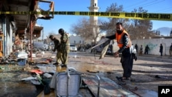 Pakistani security officials examine at the site of suicide bombing in Quetta, Pakistan, Wednesday, Jan. 13, 2016. The suicide attack on a polio vaccination center in southwestern Pakistan killed more than a dozen people and wounded many.