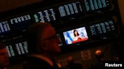 FILE - Attendants of a ceremony at Buenos Aires' Stock Exchange watch as Argentina's President Cristina Fernandez de Kirchner speaks, in Buenos Aires, Aug. 20, 2014.