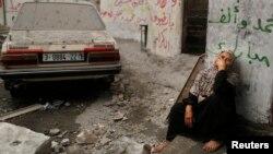 Người đàn bà Palestine ngồi nhìn căn nhà của bà đổ nát vì đạn pháo kích