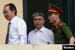 លោក Nguyen Xuan Son (រូបកណ្តាល) អតីតប្រធានក្រុមប្រឹក្សាភិបាលរបស់ក្រុមហ៊ុន Petro Vietnam ត្រូវបានប៉ូលិសនាំខ្លួនទៅតុលាការដើម្បីស្តាប់សាលក្រមនៅក្នុងក្រុងហាណូយ។