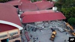 Para petugas terus melanjutkan pencarian korban di antara reruntuhan gedung yang ambruk akibat digoncang gempa di kota Porac, provinsi Pampanga, utara Filipina, 22 April 2019.