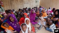 FILE - Women and children wait to participate in a vaccination campaign against meningitis at the community center in Al Neem camp for Internally Displaced People in El Daein, East Darfur, Sudan, October 8, 2012.