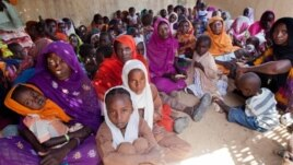 Women and children wait to participate in a vaccination campaign against meningitis at the community center in Al Neem camp for Internally Displaced People in El Daein, East Darfur, Sudan, October 8, 2012.