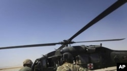 "FILE - In this Sept. 6, 2011, a U.S Army flight medic Spc. Zacharye Menzie, right, from Albuquerque N.M, along with medical nurses of U.S. Marines, carry a wounded Afghan Army soldier to a medevac helicopter from the U.S., Army's Task Force Lift ""Dust Off"