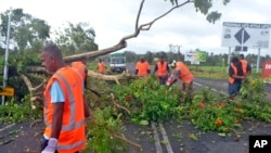 Road workers remove a fallen tree blocking a road near Lami, Fiji, Feb. 21, 2016, after cyclone Winston ripped through the country. Officials in Fiji are assessing damage in the wake of the ferocious cyclone that tore through the Pacific island chain.