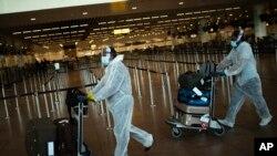 جولائی دو ہزار بیس کی اس فائل فوٹو میں مسافر کووڈ سے بچاو کا حفاظتی گئیر پہن کر ائیرپورٹ سے گزر رہے ہیں۔