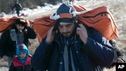 Migrants carrying their belongings walk from the Macedonian border into Serbia, near the village of Miratovac, Serbia, Jan. 19, 2016.