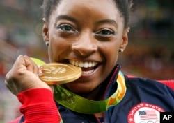 Vận động viên thể dục dụng cụ của Mỹ Simone Biles cắn chiếc huy chương vàng mà cô giành được trong phần thi toàn năng nữ ở Thế vận hội Mùa hè Rio de Janeiro, Brazil, ngày 11 tháng 8 năm 2016.