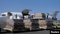FILE - Workers unload an aid shipment from a plane at the Sanaa airport, Yemen, Nov. 25, 2017.