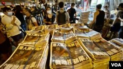 A newspaper seller in Hong Kong selling more than 10,000 copies of Apple Daily.