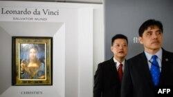 Bức hình chụp ngày 13 tháng 10, 2017 cho thấy một người đàn ông (phải, cravate xanh dương) được truyền thông Hong Kong xác định là Jerry Chun Shing Lee đứng trước một nhân viên an ninh tại buổi ra mắt bức họa 'Salvator Mundi' của Leonardo da Vinci tại phòng trưng bày của nhà đấu giá Christie ở Hong Kong.